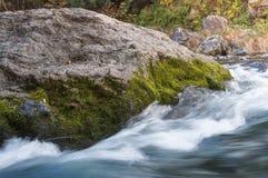 生苔花岗岩岩石ahainst快速流动的河 库存照片