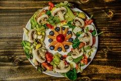 生菜盘用水果沙拉在中部在木桌上 免版税图库摄影