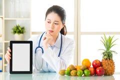 医生营养师用果子和拿着数字式片剂跌倒了 库存照片