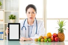 医生营养师用果子和拿着数字式片剂跌倒了 免版税图库摄影
