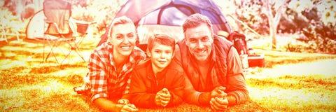 生说谎在帐篷之外的母亲和儿子在露营地 库存照片