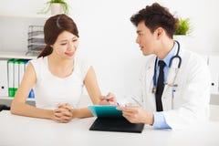 医生谈话与女性患者在办公室 库存图片
