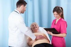 年轻医生谈话与患者 库存图片