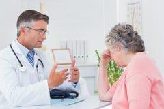 医生谈话与被拉紧的患者 免版税库存照片