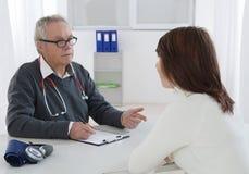 医生谈话与他的女性年轻患者 图库摄影