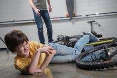 生赛跑帮助落受伤的男孩自行车 免版税库存照片