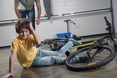 生赛跑帮助落受伤的男孩自行车 库存照片