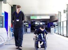 生走与轮椅的残疾儿子到医院 免版税库存图片