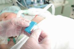 医生连接心脏起搏器到患者 免版税库存图片