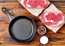生铁平底锅用在木背景的未加工的ribeye牛排 免版税库存图片