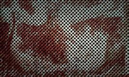 生锈的不锈的金属穿孔的表面 免版税库存照片