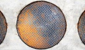 生锈的圆的人孔由一块酒吧方格的钢板制成 库存照片