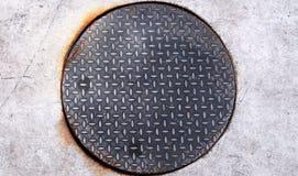 生锈的圆的人孔由金刚石钢板制成 免版税库存图片