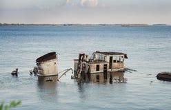 生锈的小船击毁在一条蓝色河 免版税库存图片