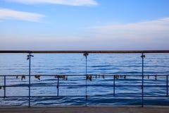 生锈的挂锁在平台被剥皮的栏杆被锁了  蓝天和海背景 库存照片