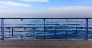 生锈的挂锁在证明爱的被剥皮的栏杆关闭了 关闭看法、蓝天和海背景 库存图片