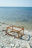 生锈的框架在海滩的一个箱子 库存图片
