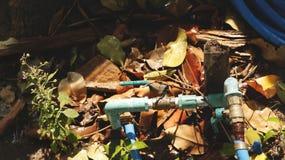 生锈的水阀门和管子在湿庭院地面与干燥叶子、草和木头 免版税库存图片