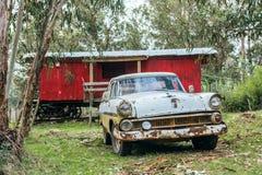生锈的汽车在一个老铁路棚车前面停放了 图库摄影