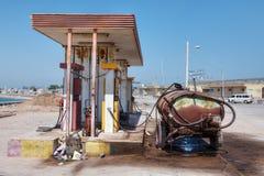 生锈的汽车坦克在一个小加油站附近站立 库存照片