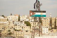 生锈的约旦旗子和阿曼大厦视图 免版税库存图片
