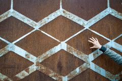 生锈的葡萄酒金属背景与金刚石样式和葡萄酒蓝色油漆和一只苗条开放女性手的 免版税库存图片