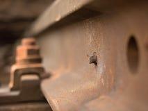 生锈的螺丝和坚果细节在老铁轨 与生锈的基本要点的腐烂的木领带 免版税库存图片