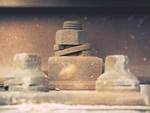 生锈的螺丝和坚果细节在老铁轨 与生锈的基本要点的腐烂的木领带 库存照片