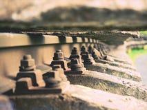 生锈的螺丝和坚果细节在老铁轨 与生锈的基本要点的腐烂的木领带 免版税图库摄影