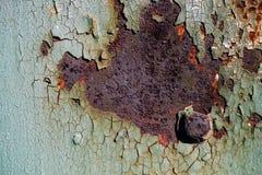 生锈的金属板料与破裂和片状油漆,与螺栓的一个金属表面,与破裂的绿色pa的抽象生锈的金属纹理的 库存照片