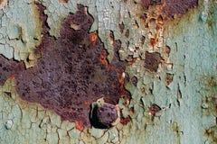 生锈的金属板料与破裂和片状油漆,与螺栓的一个金属表面,与破裂的绿色pa的抽象生锈的金属纹理的 库存图片