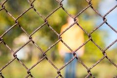 生锈的金属格栅篱芭宏指令和自然供以人员背景 库存图片