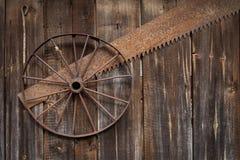 生锈的金属轮子在从老委员会的墙壁上垂悬 免版税库存图片