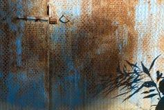 生锈的铁板料和蓝色油漆的门 免版税库存图片