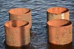生锈的铁管子在河 免版税库存图片