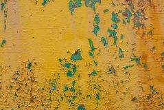 生锈的铁表面与老油漆,切削的油漆,黄色纹理,背景残余的  免版税库存照片