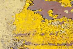 生锈的铁表面与老油漆,切削的油漆,黄色纹理,背景残余的  免版税库存图片