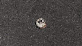 生锈的铝饮料罐头在一个黑暗的沙子海滩洗涤了,冲击环境和污染海洋和海滨 免版税图库摄影