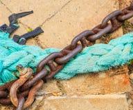 生锈的链子和蓝色绳索 库存照片