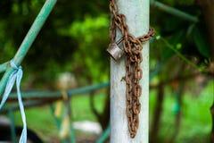 生锈的锁和链子的特写镜头图片在钢专栏有被弄脏的bokeh背景 免版税库存图片