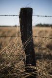 生锈的锋利的木材和金属倒钩铁丝网 库存图片