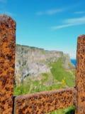 生锈的门俯视的峭壁 免版税库存照片