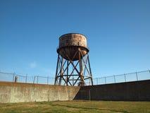 生锈的水塔在墙壁和吟呦诗人铁丝网之外站立 免版税库存图片