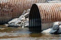 生锈的阴沟管子开头在水中 免版税库存图片
