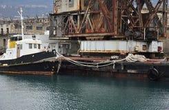 生锈的货物起重机和驳船的里雅斯特老港口,意大利 库存照片