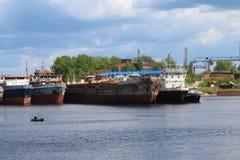 生锈的货船和孤独的渔夫小船的在夏天 免版税库存照片