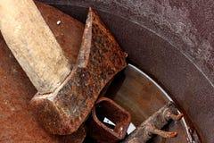 生锈的woodchopper轴、锄和犁耙在生锈的桶用水 库存图片