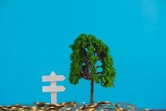 生长在堆的树金黄硬币和白色木板标志、成长企业财务投资和公司社交 免版税库存图片