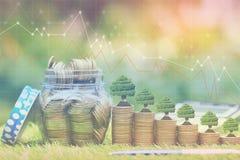 生长在绿色背景、投资和企业概念的硬币金钱和玻璃瓶的树 库存照片