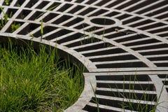 生长通过金属形状的绿草 库存图片